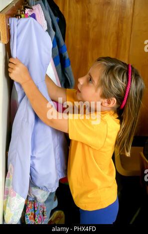 School Girl Hanging Up Jacket im Klassenzimmer HERR © Myrleen Pearson... Ferguson Cate Stockbild