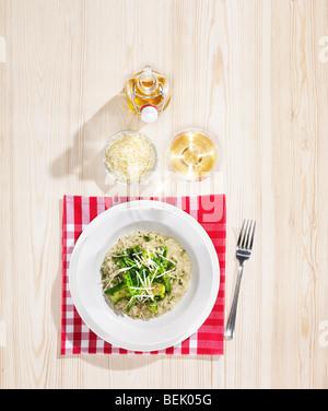 Gemüse-Risotto mit Parmesan (Parmigiano) und Olivenöl, mit einem Glas Weißwein serviert Stockbild