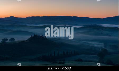 Vor Sonnenaufgang Nebel liegt in den Feldern und Hügeln der Val d'Orcia über ein Bauernhaus auf einem kleinen Felsvorsprung, UNESCO, Toskana, Italien gehockt Stockbild