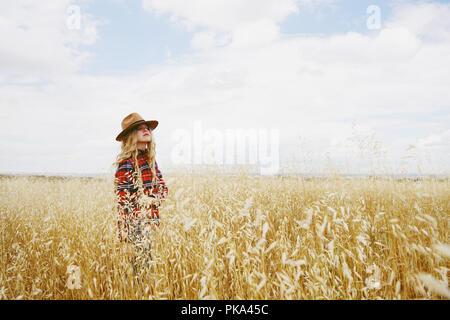 Jung und blond Land Frau possing in einem Feld von Weizen in einem Sommertag Stockbild
