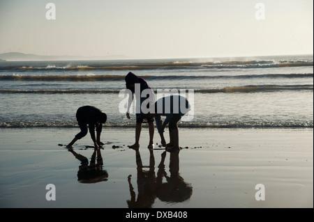 Kinder spielen am Strand bei Ebbe, Marokko Stockbild