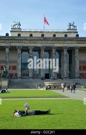 Eine junge Frau entspannt sich und liest in der Lustgarden Berlin, mit dem alten Museum im Hintergrund Stockbild