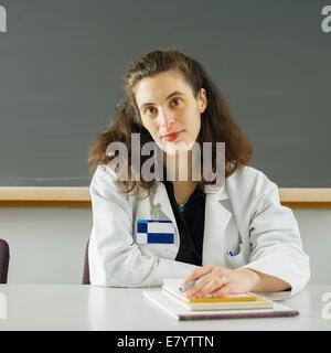 Frau sitzt am Schreibtisch im Klassenzimmer Stockbild