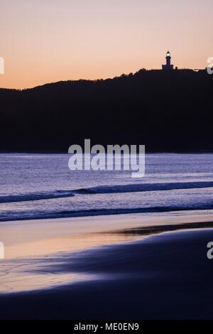Silhouette von Cape Byron Lighthouse auf einem Hügel und am Strand bei Sonnenuntergang bei Byron Bay in New South Wales, Australien Stockbild