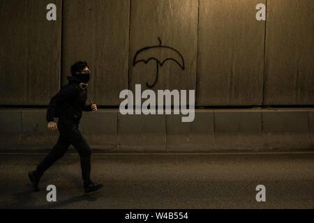 Demonstrator läuft vor Graffiti in einem Tunnel in die Zentrale nach zivilen Menschenrechte März in Causeway Bay Hongkong Demonstranten für ein weiteres Wochenende der Proteste gegen die umstrittene Auslieferung Bill gesammelt und mit einer wachsenden Liste von Beschwerden, die der Aufrechterhaltung des Drucks auf Chief Executive Carrie Lam. Stockbild