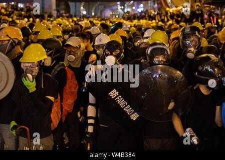 Die Demonstranten mit Helm und Gasmasken, sich von der Polizei zu protestieren. Die Hong Kong Polizei hat verwendet, Tränengas und Blase Munition gegen Demonstranten als Hunderte von Demonstranten marschierten hat die geplante Demonstration Route. Zehntausende von pro-demokratischen Demonstranten haben wöchentliche Kundgebungen auf den Straßen von Hong Kong gegen die umstrittene Auslieferung Rechnung seit Anfang Juni fortgesetzt. Stockbild