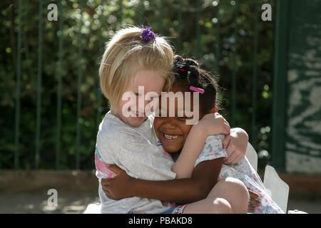 Zwei glückliche junge Mädchen umarmten einander HERR © Myrleen Pearson.... Ferguson Cate Stockbild