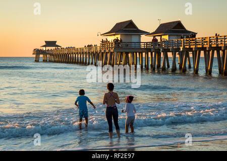 Drei Geschwister Spielen im Wasser unterhalb der Naples Pier entlang der Golfküste, Naples, Florida, USA Stockbild