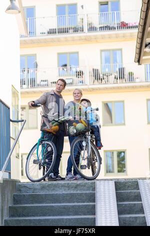 Eltern mit Sohn und Fahrräder durch den Bau Stockbild