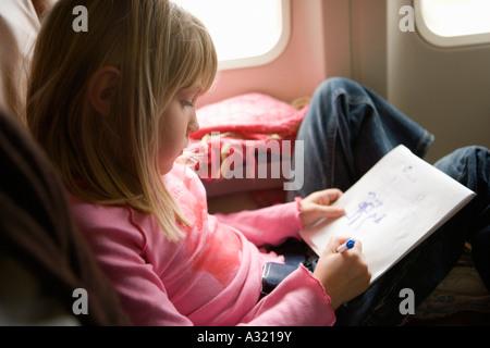 Junges Mädchen in einem Flugzeug sitzen und Zeichnung in einem Sketch pad Stockbild