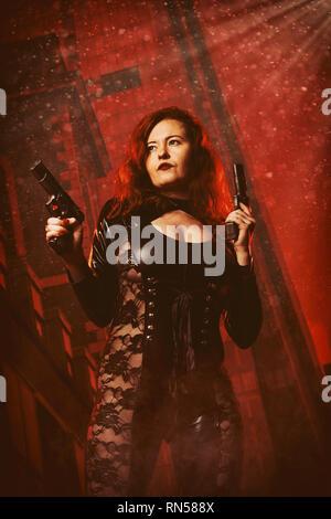 Weibliche Assassine Holding zwei Pistolen Stockbild