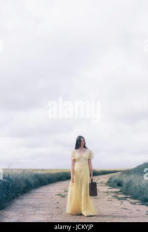 ein junges Mädchen mit einem gelben Kleid trägt einen Koffer und steht auf einem Pfad durch Getreidefeldern Stockbild