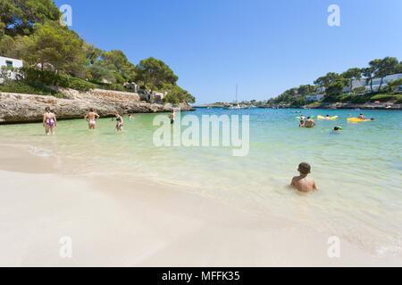 Cala d'Or, Mallorca, Spanien - August 2016 - ein Junge im Wasser sitzen am Strand von Cala d'Or Stockbild