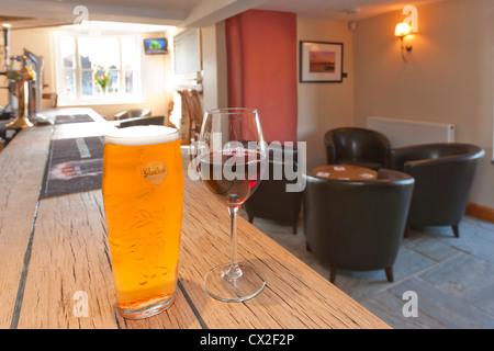 Pint Lager und Glas Rheinwein rd auf einen Balken in einem pub Stockbild