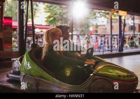 Glückliches junges Paar Stoßfänger Autofahren im Freizeitpark. Junger Mann und Frau Reiten Autoscooter Stockbild