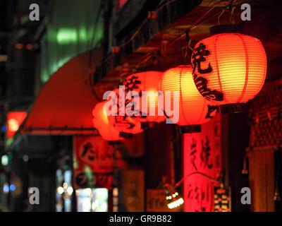Rot beleuchteten Lampions hängen außen Shop in der Nacht Stockbild