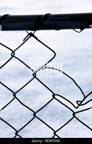 Metallische Zaun mit kleinen winzigen Wassertropfen hängen mit Schnee im Hintergrund. Stockbild