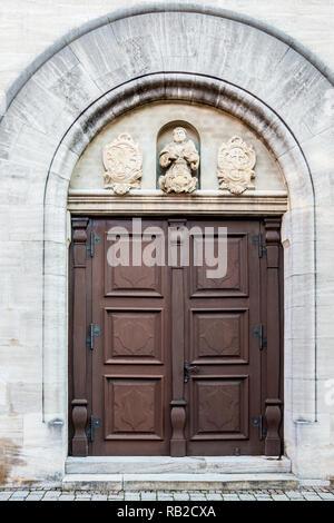 Alte Tür eines historischen Gebäudes mit Statuen und Wappen aus Stein Stockbild