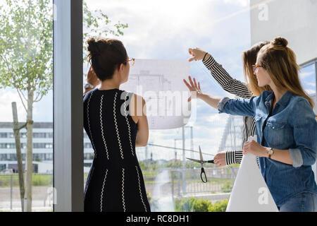 Kollegen über Pläne auf Glas Wand Stockbild