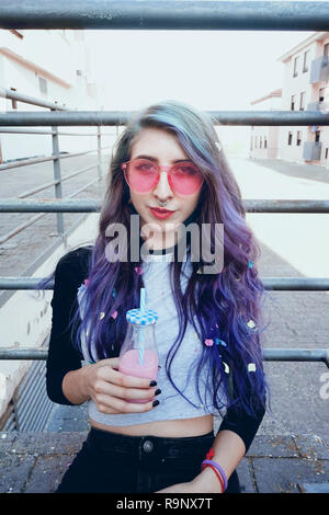 Gerne schöne jugendlich mit rosa Sonnenbrille, Getränke und genießt eine rosa Trinken sitzen auf städtischen Boden Stockbild