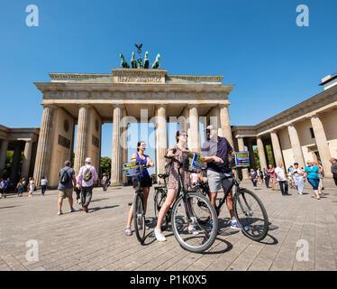 Touristen auf Fahrrädern vor dem Brandenburger Tor in Berlin, Deutschland Stockbild