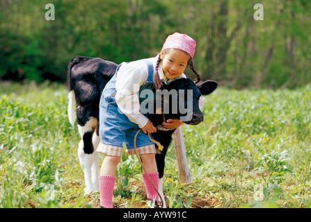 Mädchen mit schwarzen und weißen Kalb Stockbild