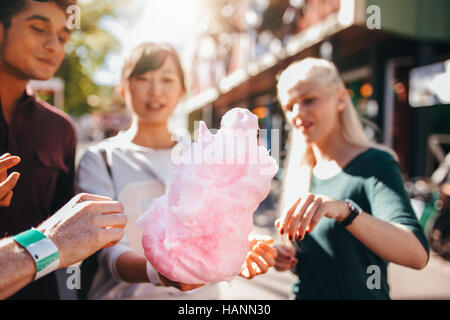 Drei junge Menschen teilen Baumwolle Zuckerwatte im Freizeitpark. Gruppe von Freunden essen Zuckerwatte zusammen Stockbild