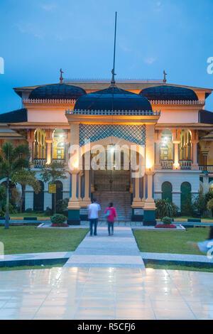 Indonesien, Sumatra, Medan, Paar zu Fuß in Richtung Maimoon Palace Stockbild