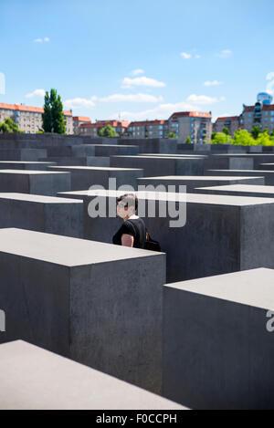 Frau zu Fuß durch das Holocaust-Mahnmal, Berlin, Deutschland Stockbild
