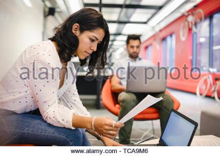 Fokussierte Geschäftsfrau mit Papierkram am Laptop arbeiten Stockbild
