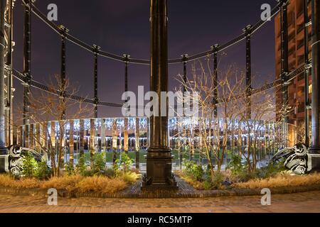 Gasspeicher Park, Kings Cross, Camden, London, 2017. Allgemeine Ansicht west Blick durch den Rahmen der Gasspeicher Nummer 8, in der Dämmerung beleuchtet. Stockbild