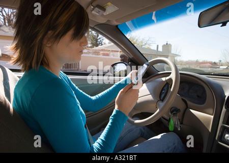 Junge Frau im Fahrersitz eines Autos sitzen und mit Blick auf Handy Stockbild