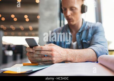Aufnahme des jungen männlichen Studenten sitzen in College-Bibliothek, die SMS-Nachricht auf seinem Handy zu Stockbild