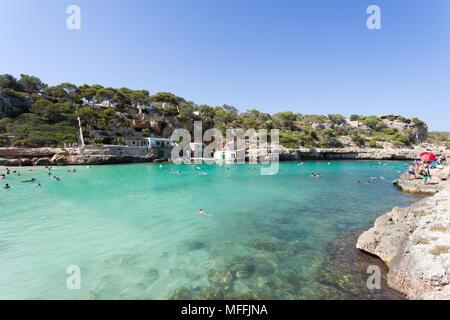Cala Llombards, Mallorca, Spanien - August 2016 - Menschen schwimmen an den Strand von Cala Llombards Stockbild