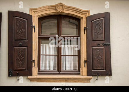 Alte Fenster aus Stein und Holz mit braunen Fensterläden Stockbild