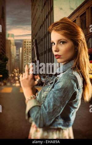 Rothaarige Frau mit einer Pistole in einer belebten Straße Stockbild