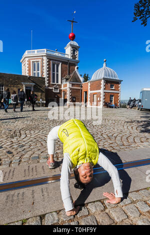 England, London, Greenwich, Royal Observatory, asiatische Touristen, die an beiden Seiten des Greenwich Meridian Line Stockbild