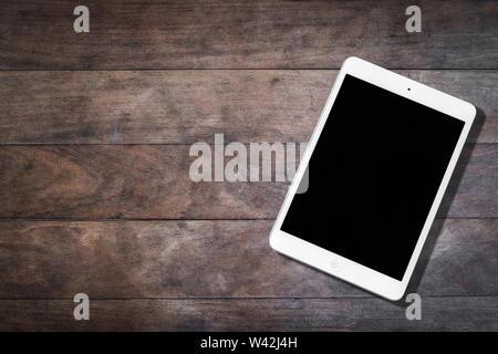 Berlin, Deutschland - Juli 2019: ein weißes apple ipad tablet mit leeren Bildschirm auf hölzernen Tisch Stockbild