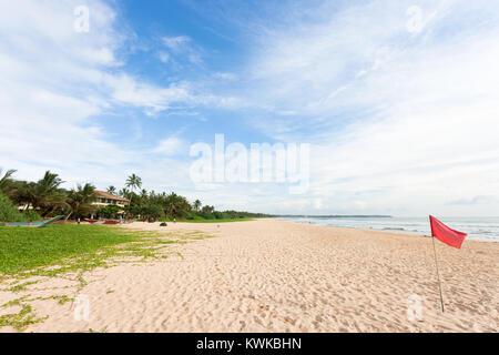 Asien - Sri Lanka - induruwa - eine rote Markierungsfahne Warnung am Strand Stockbild