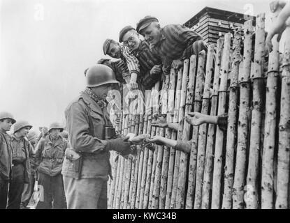GI der Siebten US-Armee gibt seinen letzten Zigaretten zu befreiten KZ-Gefangene hinter einer Einfriedung. April Stockbild