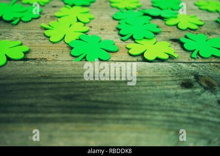 Schöne Nahaufnahmen der vielen Irischen shamrocks, fest Klee, in einer Reihe, daß Glück erinnern oder Saint Patrick's Day und hölzerne Tische als Hintergrund Stockbild