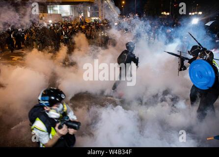 Eine Demonstrantin zu hetzen, um sie den Benzinkanister von der Polizei in ein Versuch, sie zurück zu der Polizei feuerte Tränengas zu werfen. Die Hong Kong Polizei hat verwendet, Tränengas und Blase Munition gegen Demonstranten als Hunderte von Demonstranten marschierten hat die geplante Demonstration Route. Zehntausende von pro-demokratischen Demonstranten haben wöchentliche Kundgebungen auf den Straßen von Hong Kong gegen die umstrittene Auslieferung Rechnung seit Anfang Juni fortgesetzt Stockbild