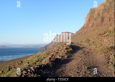 Grobe track und Fußweg entlang der Seite des Famara Klippen, mit im Hintergrund die Insel La Graciosa, Lanzarote, Kanarische Inseln, Februar. Stockbild
