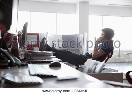 Unternehmer im Gespräch über smart phone mit Füßen auf Schreibtisch Stockbild