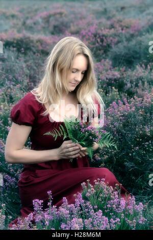 eine Frau in einem roten Kleid sitzt in die Heide mit einem Blumenstrauß Stockbild