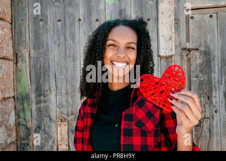 Schöne junge Frau hält ein rotes Herz Stockbild