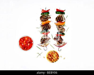 Gegrilltem Fleisch und Gemüse Kebab mit Chili-Sauce, Zitrone und Kräutern. Stockbild