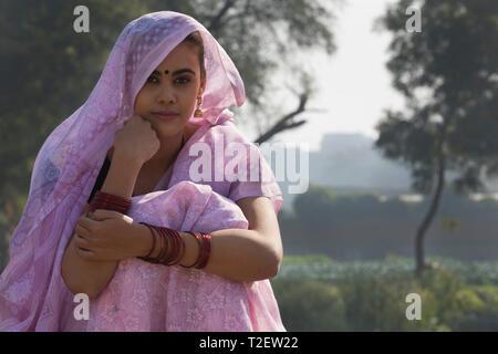 Nahaufnahme eines ländlichen Frau sitzt in der Nähe von Landwirtschaft Feld über dem Kopf mit Sari. Stockbild