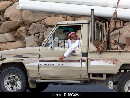 Saudi Mann, der seinen Toyota Auto Transport von Rohren, Provinz Jizan Addayer, Saudi-Arabien Stockbild