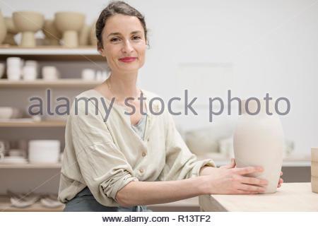 Porträt eines lächelnden jungen Frau in die Kamera zu Hause suchen Stockbild
